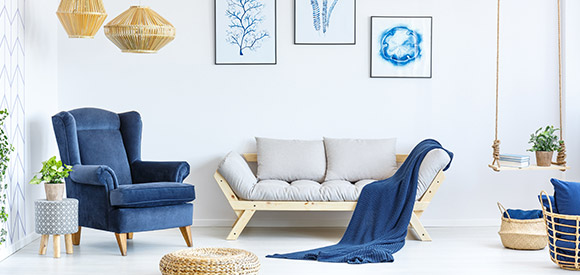 blue armchair and white timber couch with blue throw rug